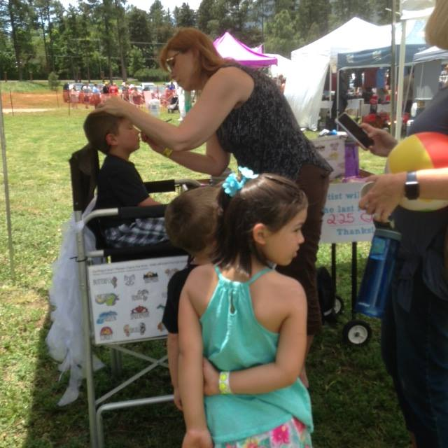 A child getting his face painted at the Colorado Springs Family Friendly Beer Festival.